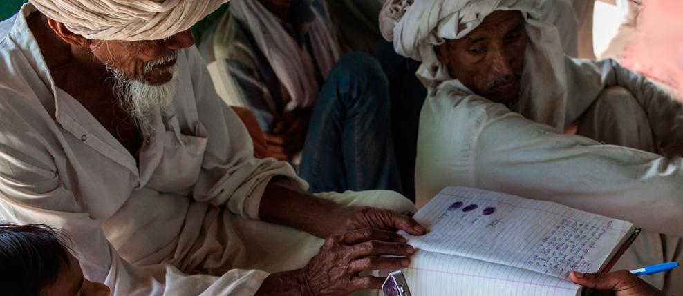 India. Alwar. During a Shiksha Panchayat meeting in Bidarka colony school. An illiterate senior member giving his thumb impression on the signature list