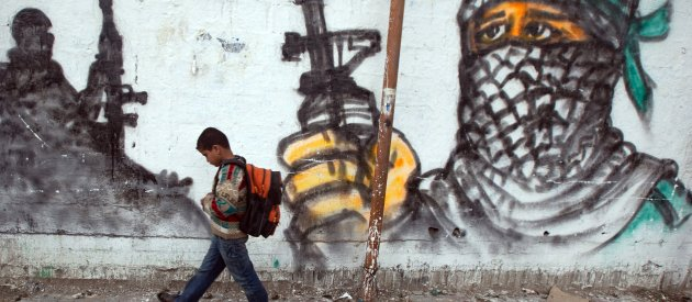 Palestinian boy passing by a grafitti as he walks to school at Jabalia area, northern Gaza Strip