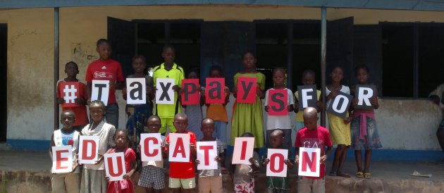 Pupils at the Activista Free Holiday Coaching Lesson in Tionsha community in Benue State Nigeria taking action as part of the Tax Power Campaign