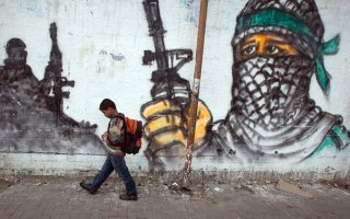 Palestinian boy passing by a grafitti as he walks to school at Jabalia area, northern Gaza Strip