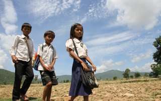 Srey Yeng, 8-year old girl, walking to school with her brothers.