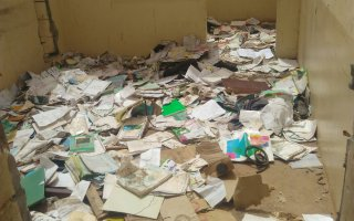 Textbooks and class materials on the floor of former school site