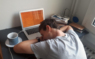 Student sleeping on laptop at desk