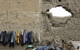 Afghan students' coats hanged on the wall destroyed by the war, Kabul, Afghanistan