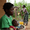 A 14-year-old girl holds her baby at her sister's home in a village in Kanduku, in Malawi's Mwanza district. She married in September 2013, but her husband chased her away. Her 15-year-old sister, in the background, married when she was 12. Both sisters s